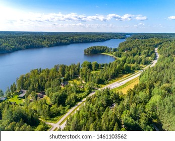 Aerial view of highway road with pine forest and blue lake in Finland