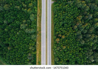 Aerial View Of Highway Road Through Green Forest Landscape In Summer. Top View Flat View Of Highway Motorway Freeway From High Attitude. Trip And Travel Concept.