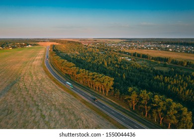 Aerial View Of Highway Road Through Field And Summer Green Forest Landscape. Top View Of Truck Tractor Unit Prime Mover Traction Unit In Motion On Freeway. Business Transportation, Trucking Industry