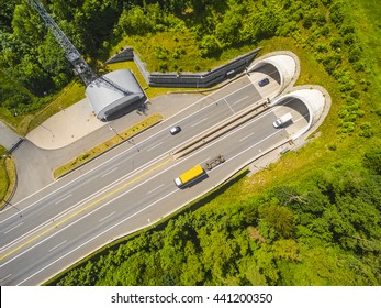 Aerial view of highway tunnel in mountains. Traffic on the road. Transportation from above. Industrial background.