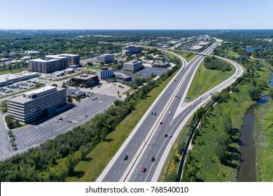 Aerial view of a highways, overpasses, ramps and buildings in a suburban Chicago suburban setting.
