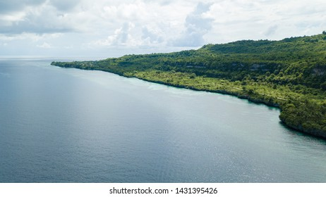 Aerial view of hill near beautiful blue ocean in Wakatobi, Indonesia, Asia