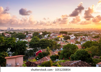 Aerial view of the historic city of Olinda in Pernambuco, Brazil at sunset contrasting with the contemporary skyscrapers of Recife in the far background.