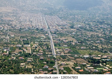 Aerial view of the historic town of Cinisi in the Palermo district of Sicily.  Surrounded by farmland and seen on a sunny summer morning.