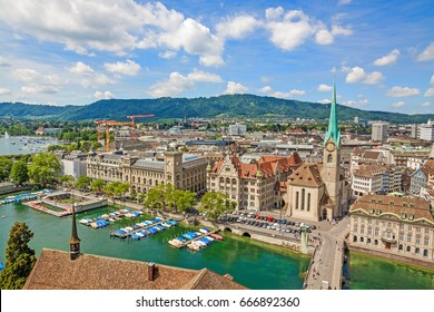 Aerial view of historic Zurich city center with famous Fraumunster Church, townhouse and river Limmat at Lake Zurich from Grossmunster Church on a sunny day with clouds in summer, Switzerland