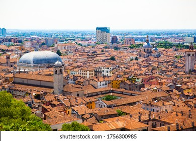 Aerial view of the historical center of Brescia (Lombardy, Italy) with tiled red roofs, chimneys, cathedral's domes and tall white brick old towers. Traditional European medieval architecture.