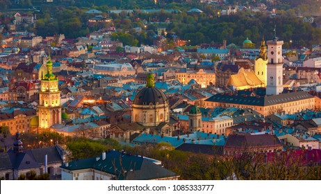 Aerial view of historical old city district of Lviv, Ukraine. Time between sunset and night, city street lights are lit. Churches, cathedrals, city hall and houses roofs in old lviv.