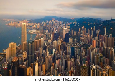 Aerial view of Hong Kong Downtown, Republic of China. Financial district and business centers in smart city in Asia. Top view of skyscraper and high-rise buildings at sunset.