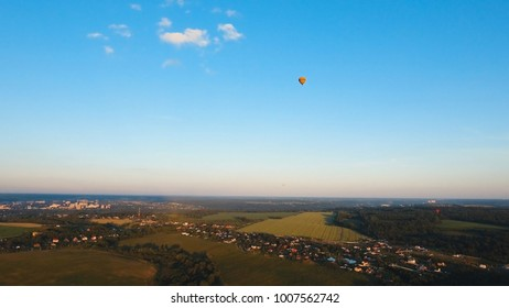 Aerial view Hot air balloon in the sky over a field in the countryside in the beautiful sky and sunset. Aerostat fly in the countryside. Aerial footage
