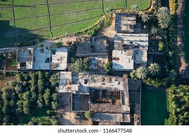 Aerial view from hot air balloon of roof top of houses and farms with the light of sunrise in Luxor, Egypt
