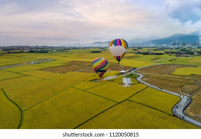 Aerial view of hot balloons fly over rice fields at sunrise moment, DonShan, YiLan, Taiwan.