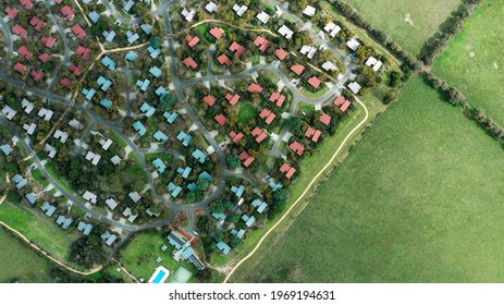 Aerial view of house in Phillip Island village, blue and red roof top. Interesting combination of house next to green farm in summer season.
