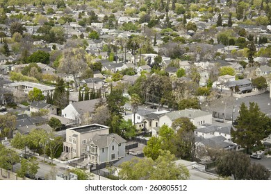 An aerial view of houses and buildings in an urban neighborhood.  Selective color emphasizes the urban forest.