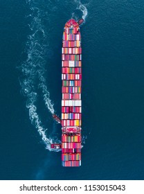 Aerial view of a huge container ship leaving port while being assisted by three tug boats