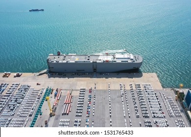 Aerial view of the huge ro-ro ship loading new cars. Automotive container carriers oversea services. Transportation business for prefabricated cars by sea freight.