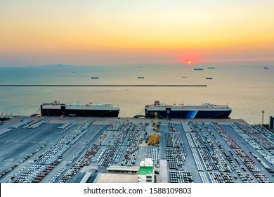 Aerial view of the huge ro-ro ship loading new cars at sunset. Automotive container carriers oversea services. Transportation business for prefabricated cars by sea freight
