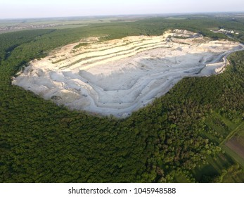 Aerial view of the huge white industrial lime-pit for the production of cement and lime (a limestone quarry) on the top of a mountain overgrown with wood.  Opencast mining quarry. Deforestation