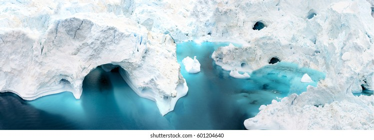 aerial view of the icebergs on arctic ocean at Greenland. Glaciers are melting at north circle of the world. Climate change to close future.