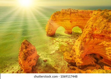 Aerial view of iconic natural arches of Praia da Marinha in Algarve, Portugal, Europe. Sunbeams over Marinha Beach, one of the 100 most beautiful beaches in the world. Famous place for summer holidays