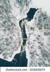 Aerial view of Icy river flowing through a beautiful snowy winter scenery in Oulanka National Park. Ruka, Finland. Drone photography
