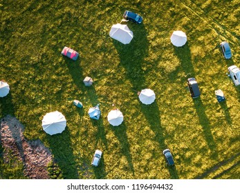 Aerial view of idyllic campsite at sunset with North London countryside as the backdrop. Bell tents and camper vans make up a trendy camping field taken from above by drone.