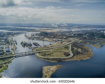 Aerial view with industrial city landscape, river, roads and cloudy sky in the background.