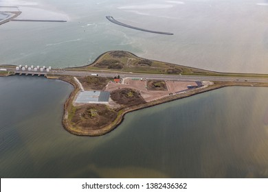 Aerial view industrial storage area near Den Oever at Dutch dike Afsluitdijk, separation between the fresh water lake IJsselmeer and the salt Wadden Sea