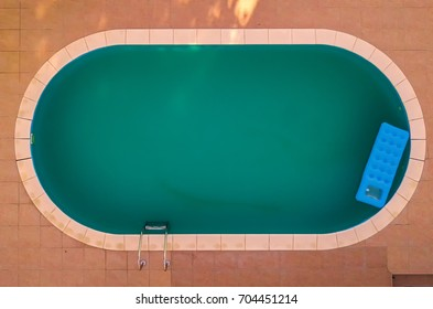 Aerial view of inflatable mattress in swimming pool - summer fun and enjoyment leisure activity equipment in the poolside water from drone point of view