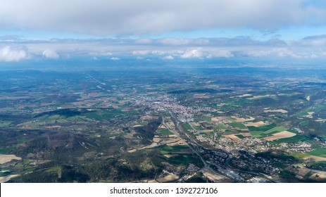 Aerial view of the intersection of French Val de Drôme with the Rhône valley with the city of Crest, France. It is a clear but cloudy day, which gives dark cloud shades in the beautiful nature area.