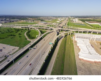 Aerial view Interstate 10 or Katy freeway with massive intersection, stack interchange, elevated road junction overpass in daytime with clear blue sky. Aerial metropolitan area of Katy, Texas, US.