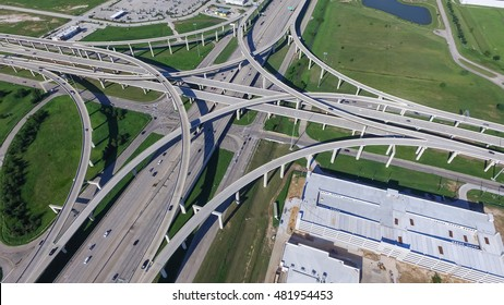 Aerial view Interstate 10 or Katy freeway with massive intersection, stack interchange, elevated road junction overpass in daytime. Nightly degree vertical view metropolitan area of Katy, Texas, US.