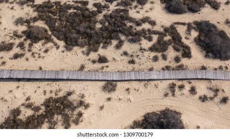 Aerial view into wooden path crosses a sand dune