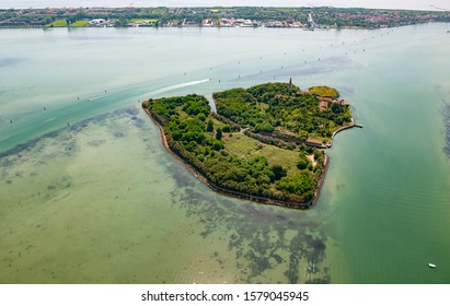 Aerial view of the island of Poveglia in the Venetian lagoon, opposite Malamocco along the Canal Orfano, which connects the mouth of the port of Malamocco with Venice, Italy, Europe