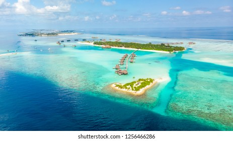 Aerial view of island resort water bungalows with blue lagoon In Maldives.