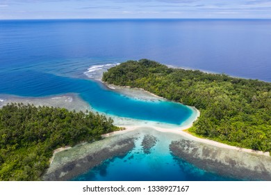 Aerial view of islands and coral reefs in Papua New Guinea. The remote, tropical islands in this region are home to extraordinary marine biodiversity and are part of the Coral Triangle.