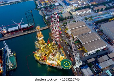 Aerial view of a jack up oil drilling rig and dry dock ship in the shipyard for maintenance during suset time