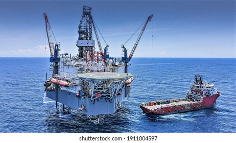 Aerial view of a jack up rig with a supply vessel during cargo operation at location.