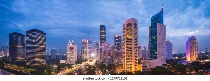 Aerial view of Jakarta's Central Business District at dusk (blue hour). Jakarta cityscape at sunset. A panorama stitched from 3 photos. Jakarta cityscape. Widescreen photo.