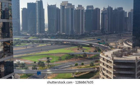 Aerial view to JLT and Dubai Marina with big highway intersection timelapse on sheikh zayed road and skyscrapers in the distance. Top view from Media city at sunrise