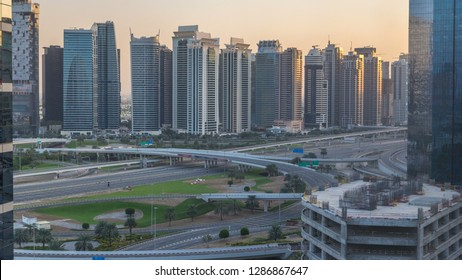 Aerial view to JLT and Dubai Marina with big highway intersection timelapse on sheikh zayed road and skyscrapers in the distance. Top view from Media city at sunset