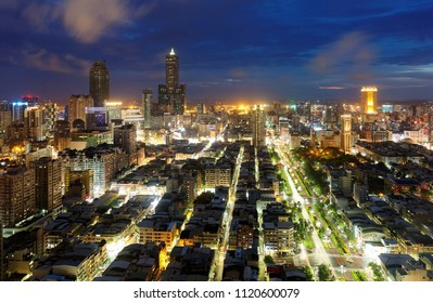 Aerial view of Kaohsiung City at dusk, a vibrant seaport in South Taiwan, with the famous landmark 85 Sky Tower standing by the harbor in background and street lights dazzling in blue evening twilight