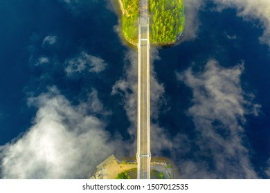 Aerial view of Karisalmi suspension bridge, Paijanne National Park, southern part of Lake Paijanne. Landscape with drone. Blue lakes, fog, bridge and green forests from above in Finland