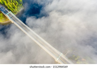 Aerial view of Karisalmi suspension bridge, Paijanne National Park, southern part of Lake Paijanne. Landscape with drone. Blue lakes, fog, bridge and green forests from above in Finland.