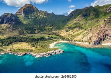 Aerial view of Kauai from a doors off Helicopter tour with lush green mountains and deep blue sea and a secluded beach