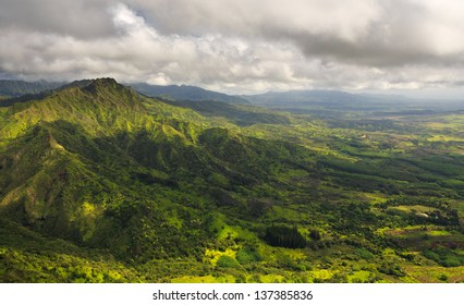 Aerial View of Kauai overlooking a green valley with a large mountain top