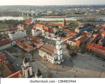 Aerial view of a Kaunas old town city hall square lit by an sunset light with city panorama in the background.