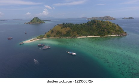 Aerial view of Kelor Island in Komodo National Park Flores Indonesia with some boats parking around the island, a clear water beach and beautiful underwater makes possible to swim and snorkeling