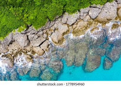 Aerial view of Kenting at sunset in Taiwan. Aerial seascape with coral reef, clear blue water, waves in summer. Transparent water. Top view. boat go through seashore. Kenting, Pingtung, Taiwan