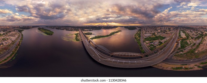 Aerial view of the Kiev city, Ukraine. Dnieper river with bridges in sunset. Darnitskiy bridge