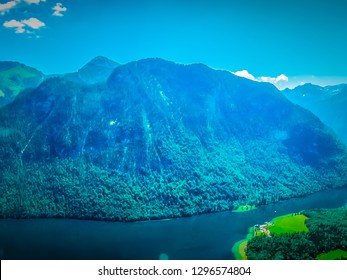 Aerial view of Koenigsee lake in Bavarian Alps on a bright sunny day with German Alps mountains in the background. Stunning panoramic view of a clear blue lake with green forest mountains from above.